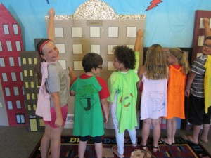 a group of super hero kids pretend to fly over buildings