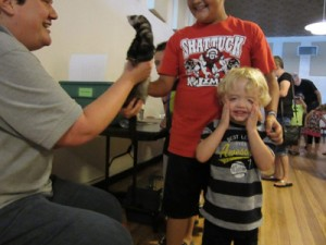 wildlife expert holds up a critter and a little boy has his hands on his face - like oh man.